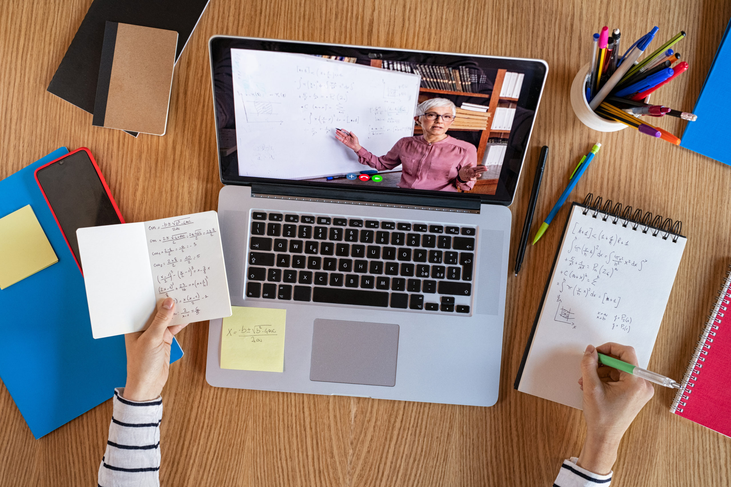 High angle view of video conference with teacher on laptop at home. College student learning maths while watching online webinar, listening audio course. Top view of girl in video call with personal tutor on computer, distance and e-learning education concept.